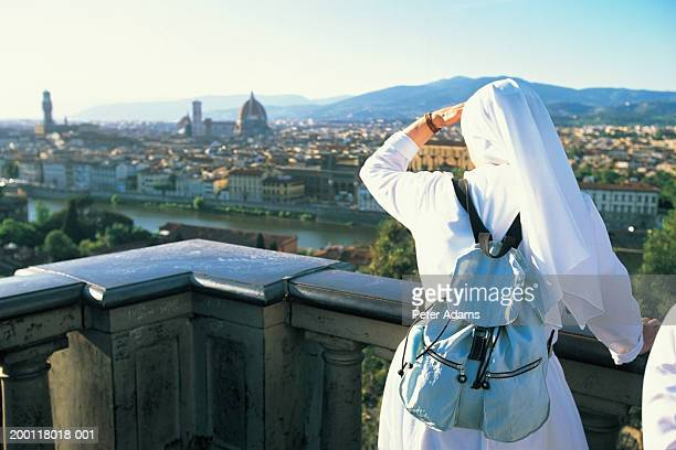 Italy, Tuscany, Florence, nun looking at view of city, rear view