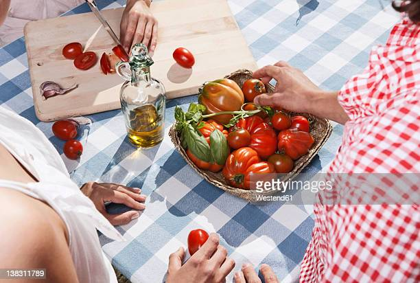 Italy, Tuscany, Magliano, Young woman cutting tomatoes on table with friends in foreground