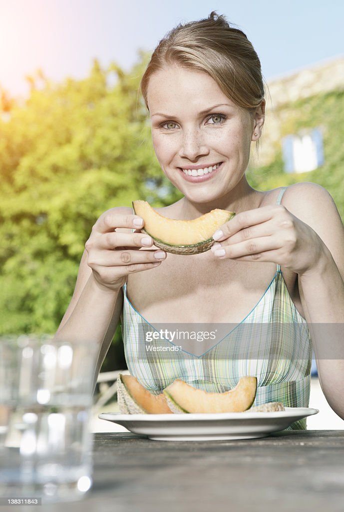 Italy, Tuscany, Magliano, Young woman holding honey melon, smiling, portrait