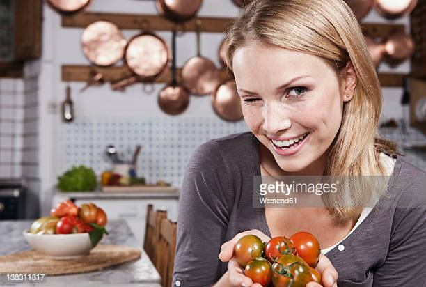 Italy, Tuscany, Magliano, Young woman winking and holding tomatoes in kitchen, smiling, portrait