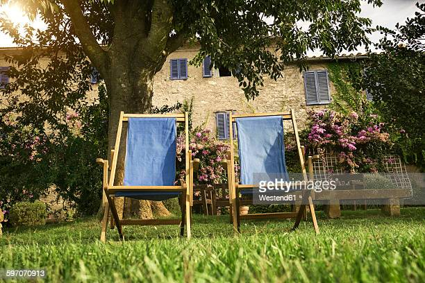 Italy, Tuscany, Maremma, Deck chairs in flowering garden of a country house