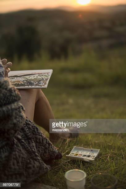 Italy, Tuscany, Maremma, woman painting sunset in rural landscape