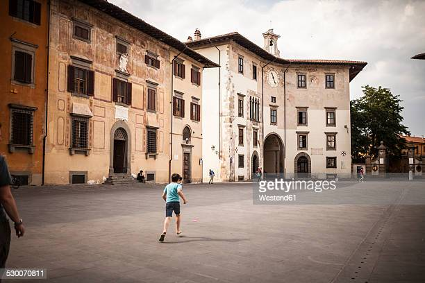 Italy, Tuscany, Pisa, Knights' Square, boy playing football with litter