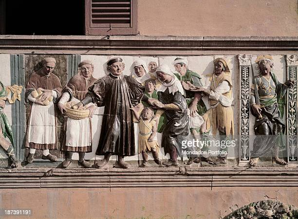 Italy Tuscany Pistoia Ospedale del Ceppo Detail Decorative frieze depicting a welltodo man making good deeds with his attendants' help he gives...