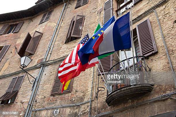 Italy, Tuscany, Siena, Different flags on a balcony