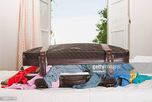 Italy, Tuscany, Stuffed suitcase on bed in hotel room