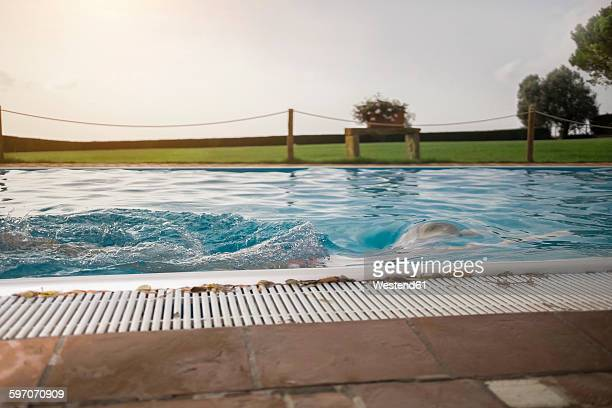Italy, Tuscany, Woman swimming in pool