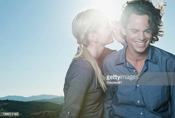 Italy, Tuscany, Young woman whispering in man's ear against sun