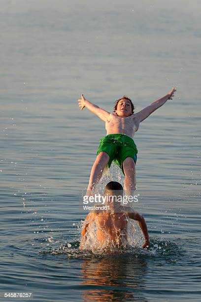 Italy, two teenage boys having fun at seaside