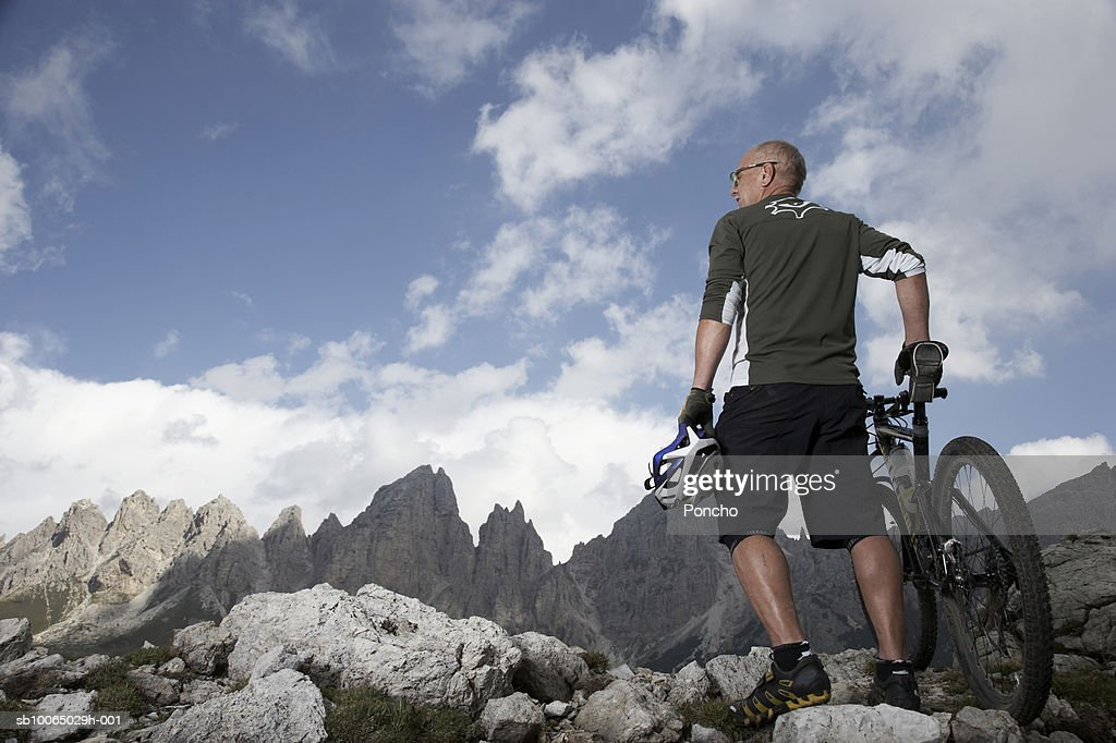 Italy, Tyrol, senior biker looking at view in mountains, low angle view, rear view : Stock Photo