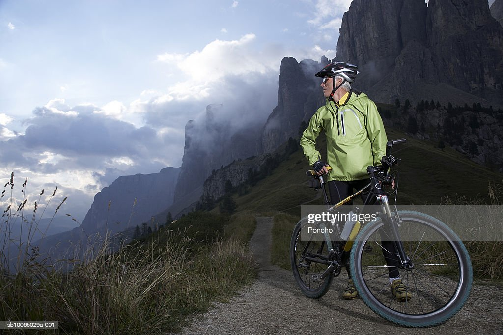 Italy, Tyrol, senior biker looking at view in mountains : Stock Photo