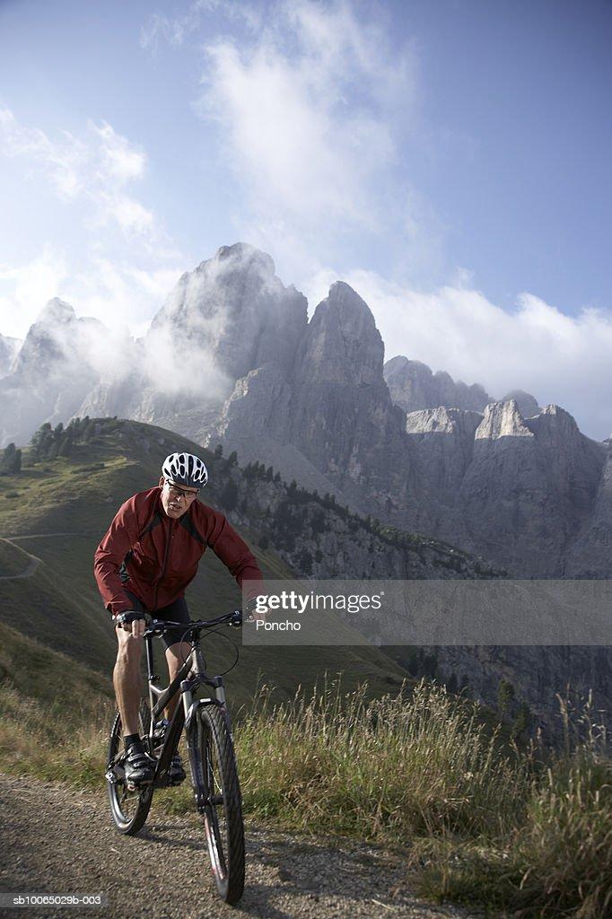 Italy, Tyrol, senior biker riding on mountain ridge : Stock Photo