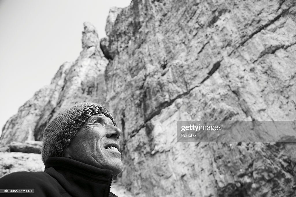 Italy, Tyrol, senior hiker looking up at rock, low angle view : Stock Photo