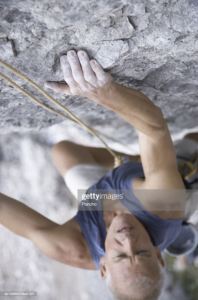 Italy, Tyrol, senior man rock climbing, view from above : Stock Photo