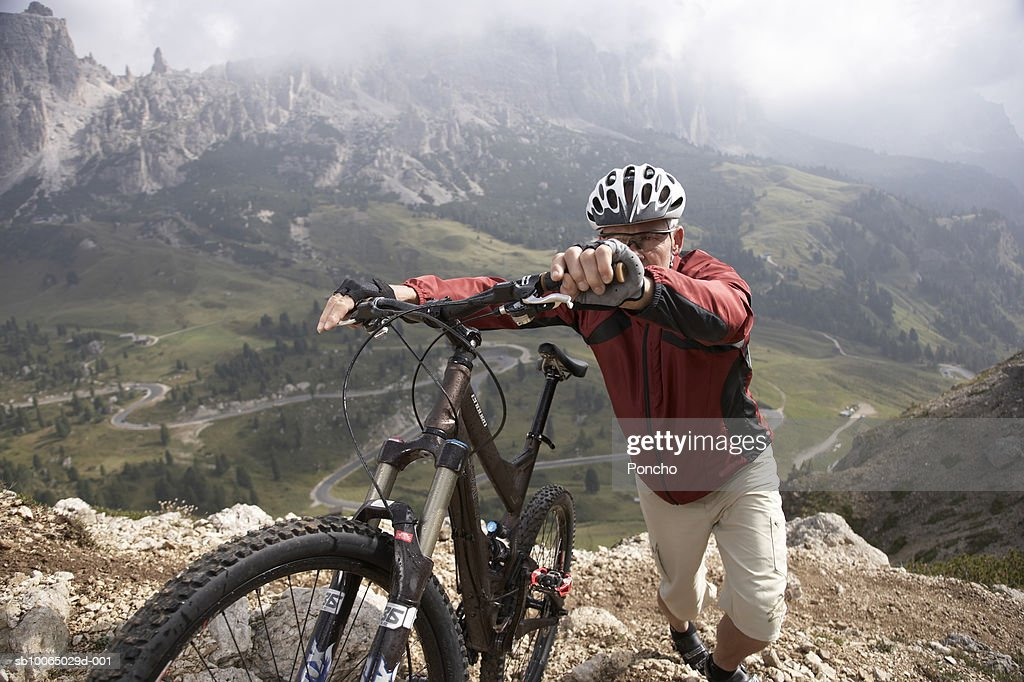 Italy, Tyrol, senior rider pushing bicycle up mountain ridge, elevated view : Stock Photo