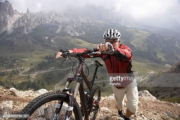 Italy, Tyrol, senior rider pushing bicycle up mountain ridge, elevated view