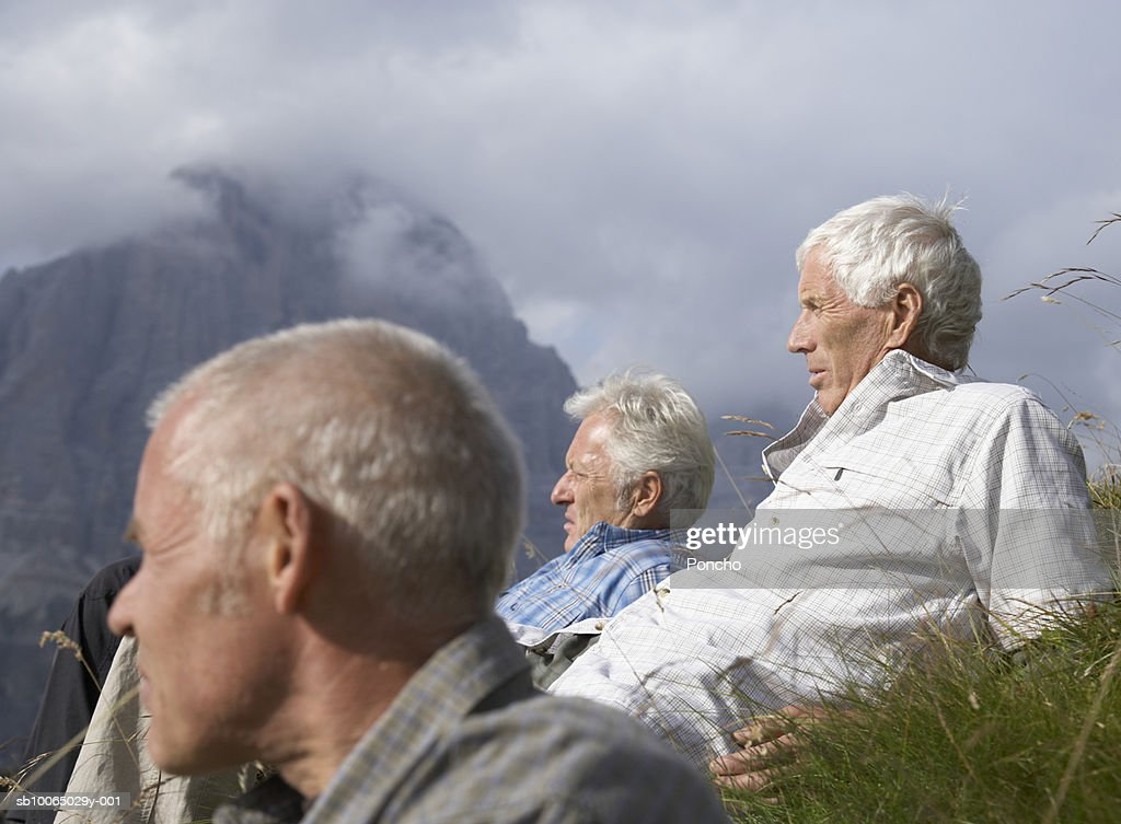 Italy, Tyrol, three senior hikers resting on grass in mountains, side view : Stock Photo