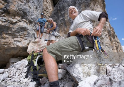Italy, Tyrol, three senior men climbing mountain, low angle view : Stock Photo