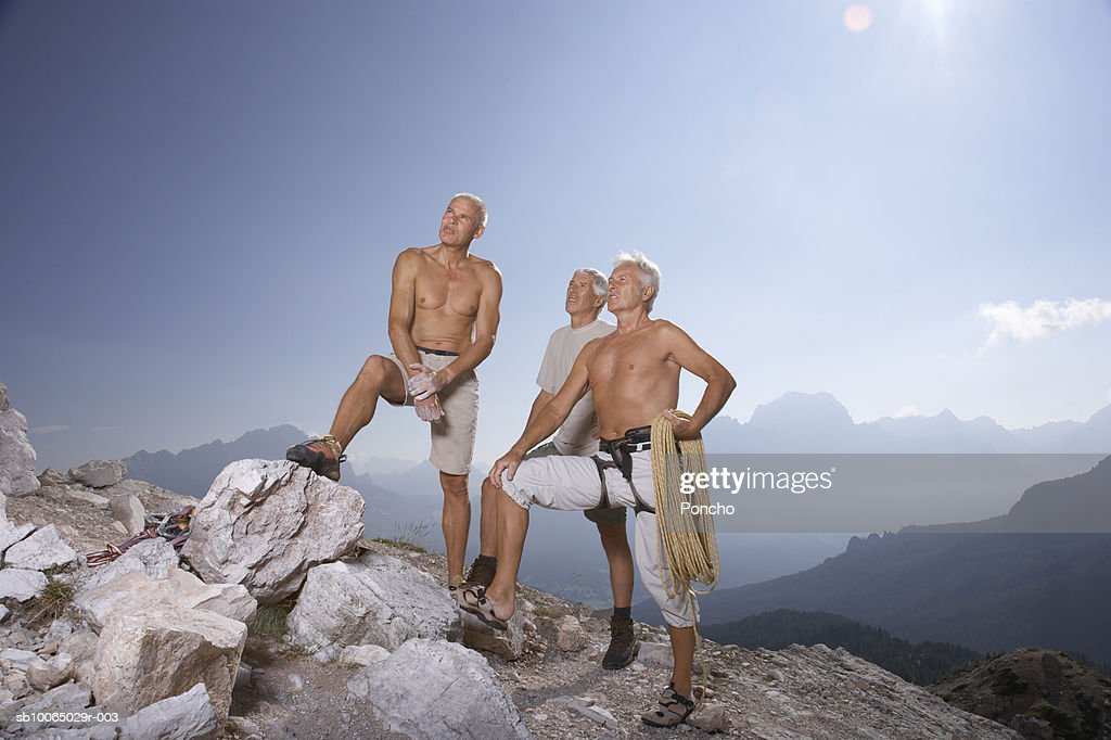 Italy, Tyrol, three senior mountain climbers standing on rocky mountain : Stock Photo