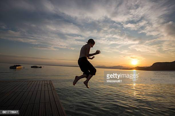 Italy, Veneto, Bardolino, Lake Garda, boy jumping into the water at sunset