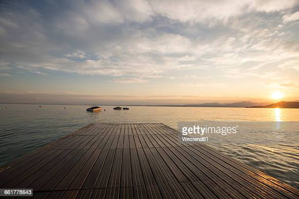 Italy, Veneto, Bardolino, Lake Garda, Pier at sunset