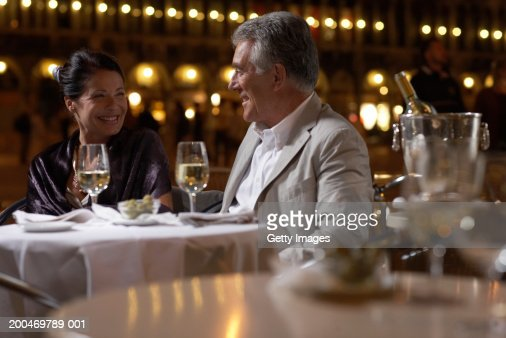 'Italy, Venice, couple at restaurant table at night, outdoors'