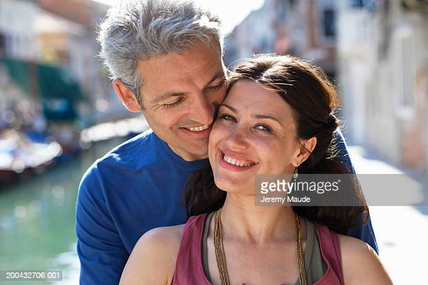 Italy, Venice, couple by canal, smiling, portrait, close-up
