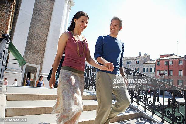 Italy, Venice, couple crossing bridge, holding hands and smiling