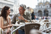 Italy, Venice, couple drinking champagne at cafe table, outdoors