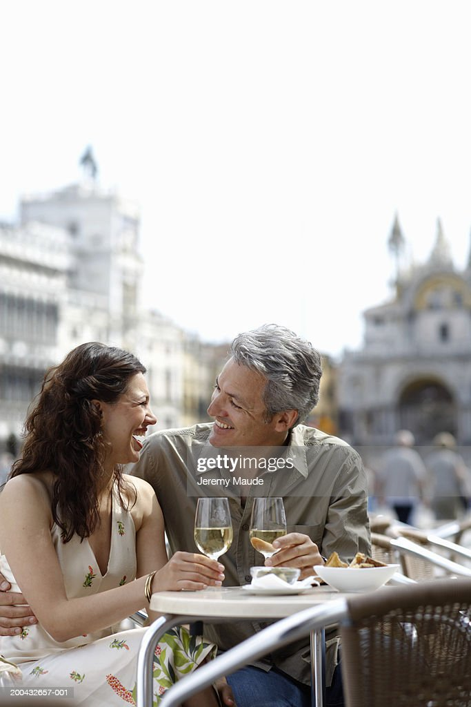 Italy, Venice, couple drinking wine at cafe table, laughing