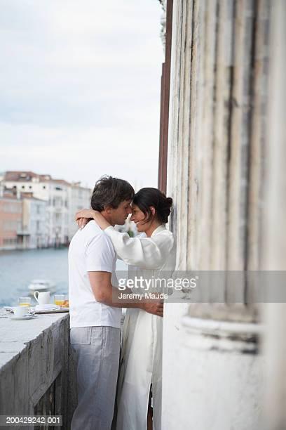 Italy, Venice, couple embracing by breakfast tray on balcony