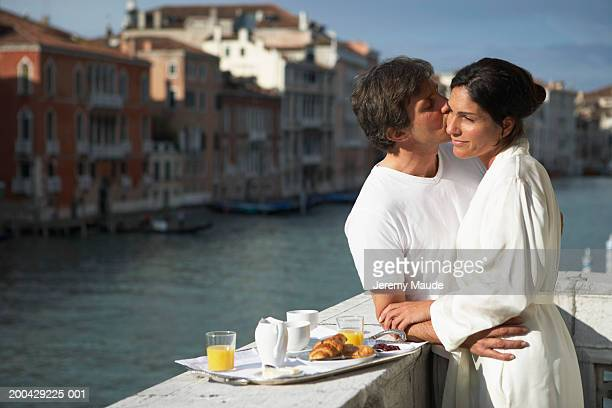 Italy, Venice, couple embracing on balcony by breakfast tray