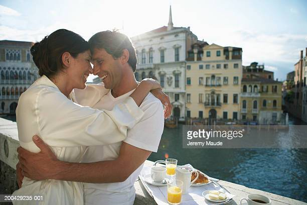 Italy, Venice, couple embracing on balcony by breakfast tray, smiling