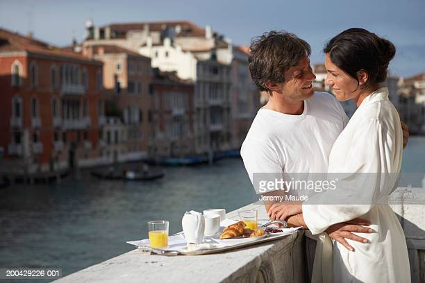 Italy, Venice, couple having breakfast on balcony, embracing