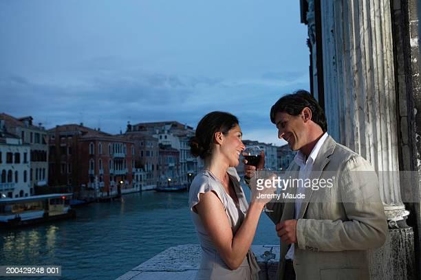 Italy, Venice, couple having drinks on balcony, smiling, dusk