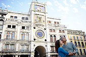 Italy, Venice, couple in front of Clock Tower in St Mark's Square