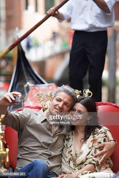 Italy, Venice, couple in gondola, man taking photograph