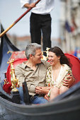 Italy, Venice, couple in gondola, man's arm around woman