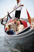 Italy, Venice, couple in gondola, smiling at each other