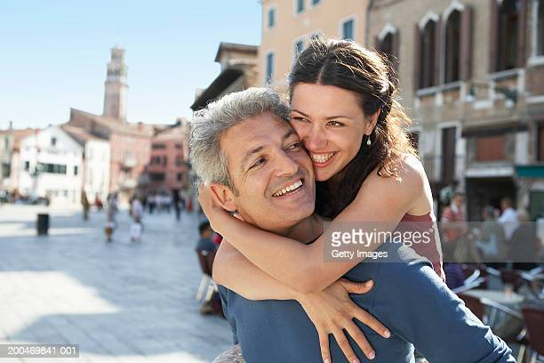 Italy, Venice, couple in street, man carrying woman on back, smiling
