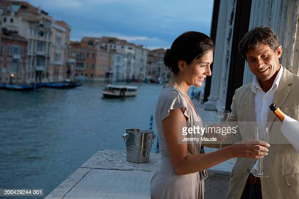 Italy, Venice, couple on balcony, man pouring champagne, dusk