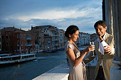 Italy, Venice, couple on balcony, man pouring champagne, smiling, dusk