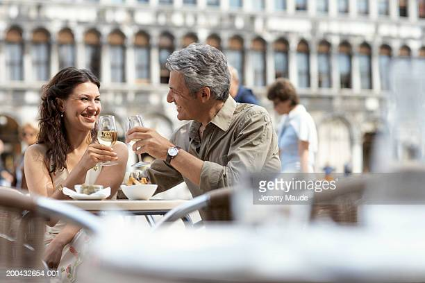 Italy, Venice, couple raising glasses at cafe table, outdoors