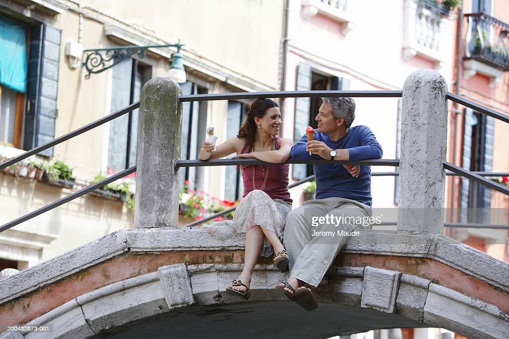 Italy, Venice, couple sitting on bridge holding ice cream cones