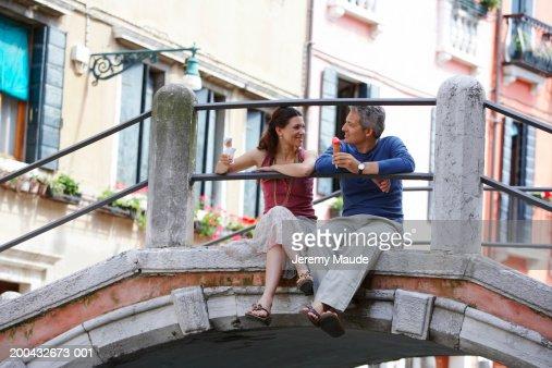 Italy, Venice, couple sitting on bridge holding ice cream cones : Stock Photo