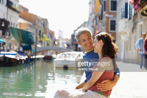 Italy, Venice, couple sitting on edge of canal, man's arm around woman