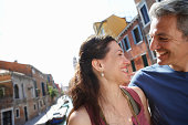 Italy, Venice, couple smiling at each other by canal, close-up