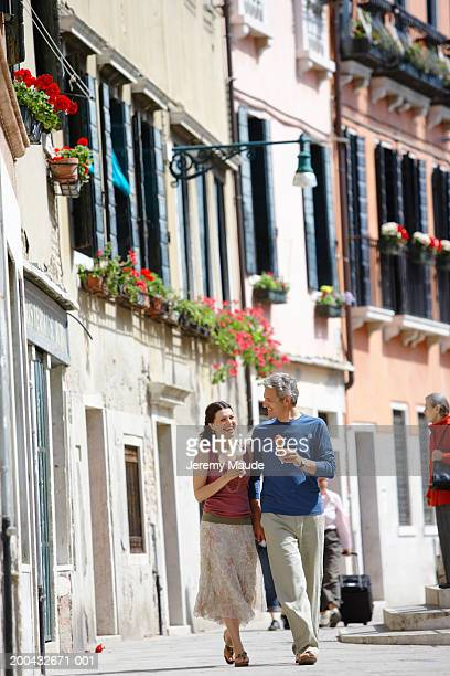 Italy, Venice, couple walking in street holding ice cream cones