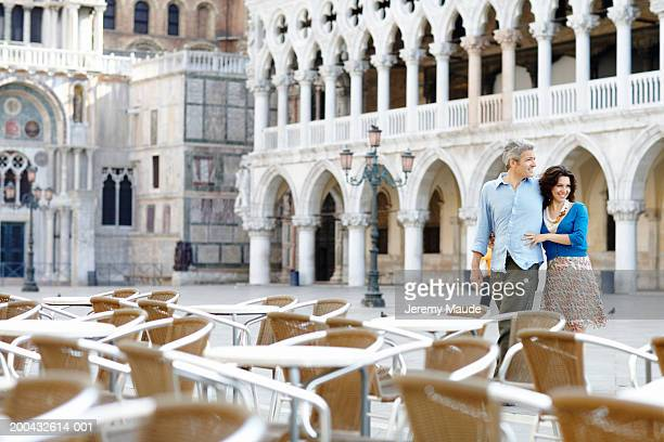 Italy, Venice, couple walking towards cafe with outdoor seating