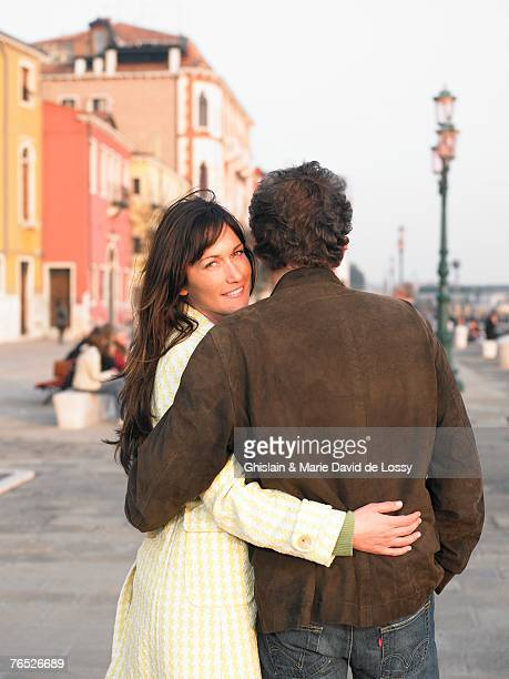 Italy, Venice, couple walking, woman smiling